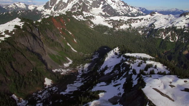 Flying Over Mountain Valley to Reveal Snowy Peak on Sunny Day video
