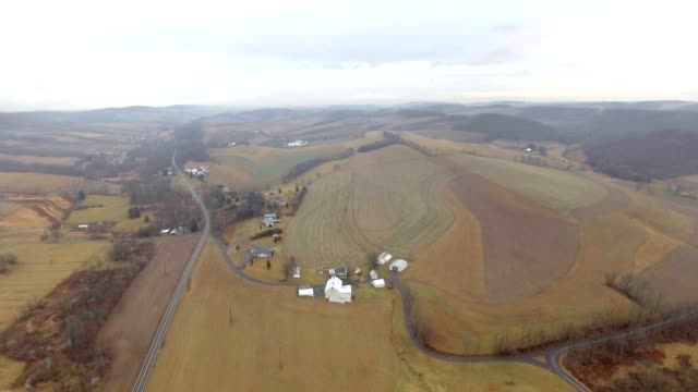 Flying over rolling hills of farmland on a cloudy day video