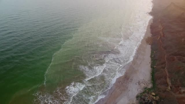 Flying over sea coast with rocky mountains on sunset video