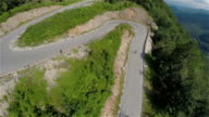 Flying over serpentine corners going downhill with few skateboarders video