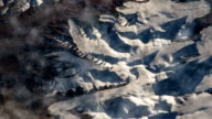 Flying over the earth on the ISS. Flying over the snow-capped mountains, aerial view from space. video