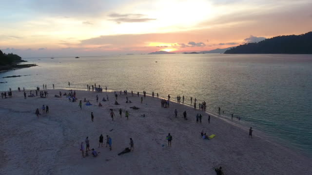 Flying over the Traveler crowd + clean sea surface at sunset or sunrise at Lipe island. video