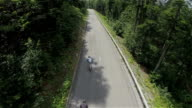 Flying over two longboarders speeding down the road in woods video