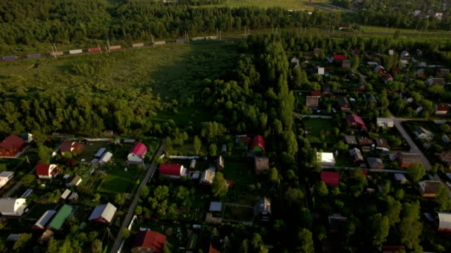 Flying over village houses and moving cargo train video