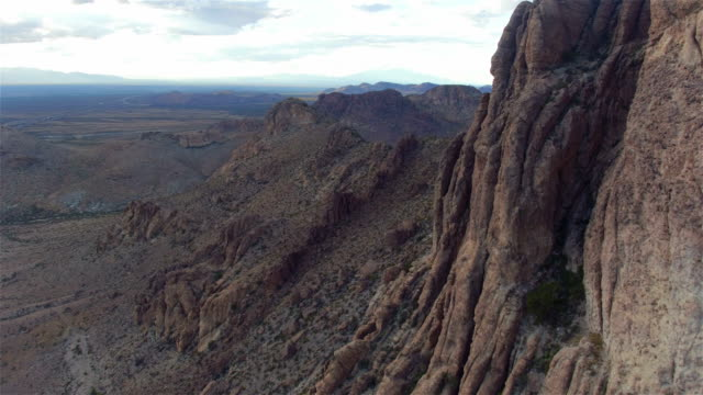 AERIAL: Flying pass rocky mountain wall in vast desert video