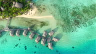 AERIAL: Flying towards and above stunning exotic white sandy beach with empty sun lounger daybeds at secluded luxury hotel resort facing big beautiful turquoise-blue lagoon video