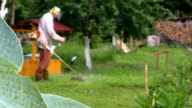 focus change to man trimming grass near water well video