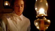 Focus moves from oil lamp to pioneer woman writing letter video