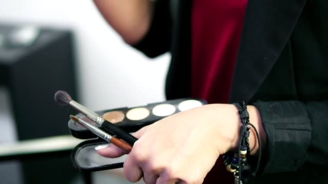 Focus moving from box with eyeshadows of different colours to the closeup view of makeup artist applying eyeshadow on eyelid using makeup brush. Professional makeup. Slowmotion shot video