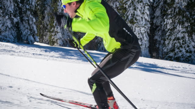 Focused cross country skier skate skiing uphill alongside a forest video