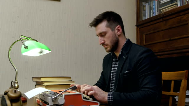 Focused journalist typing an article on typewriter sitting at the desk with green lamp video