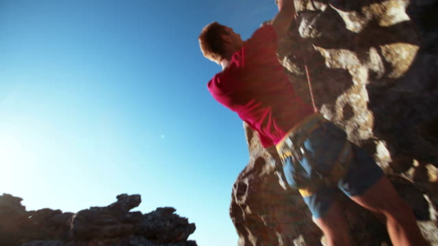 focused Rock climber holding on grip while hanging from boulder video