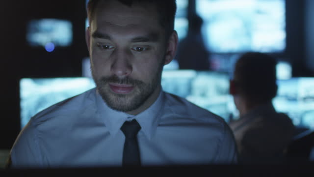 Focused security officer is working on a computer in a dark monitoring room filled with display screens. video