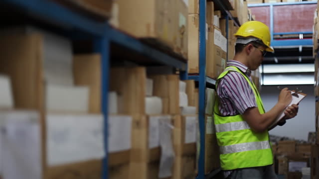 Focused warehouse male writing on clipboard in a warehouse video