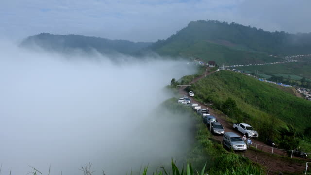 Fog rolls across flowing over Mountains with many people. video