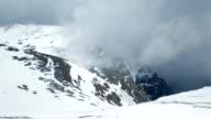 Fog surrounding snowy mountain peak, time lapse video