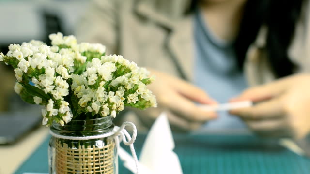 Fold a piece of paper behind white small flowers in decorated vase video