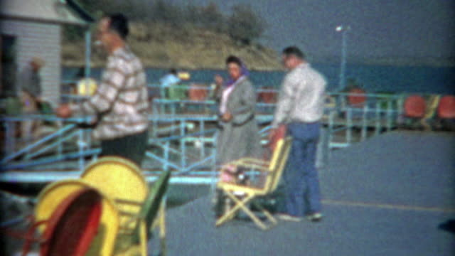 1964: Folks fishing off colorful pier in blue waters lake. video