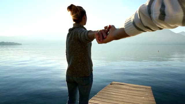 Follow me concept-Woman holding man's hand on lake pier, Italy video