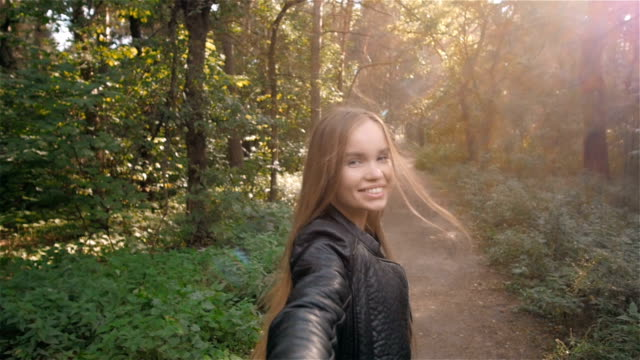 Follow me girl concept. Young pretty happy student model smiling and walking in park. healthy student lifestyle video
