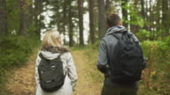 Follow shot from the back of a couple walking in an autumn forest with backpacks. video