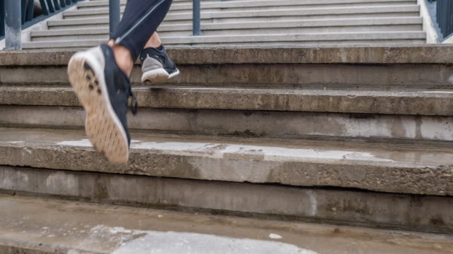 Following a young male athlete running up the stairs video