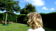 following blonde baby running in garden slow motion video