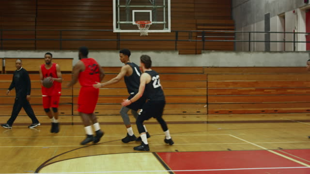 Following the action of basketball players on the court during a game, player makes a basket video