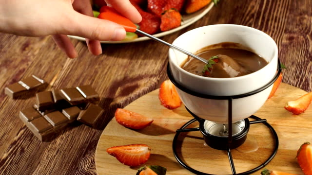 Fondue. girl takes the red strawberries on a fork dunks in hot chocolate from the fondue video