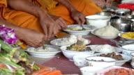 food and drink for monks in traditional religious ceremony in a temple , Thailand. video