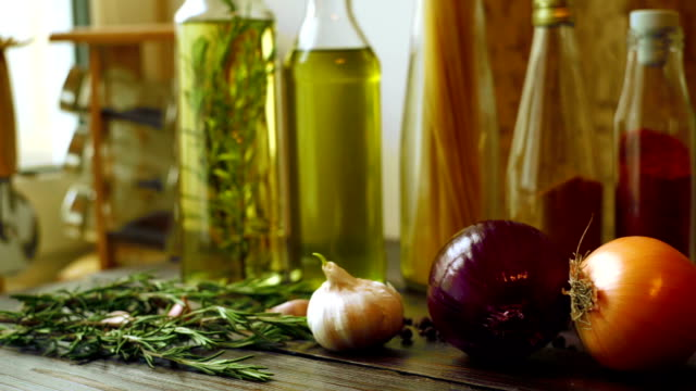 Food ingredients on kitchen table. Closeup of onion, garlic and rosemary herb video