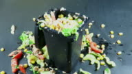 Food is thrown over a salad filled plastic trash can container , creating a mess all around, conceptual footage about modern food waste, against a black background video