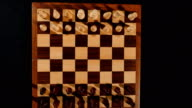 Footage of a chess board, a shot from above and it´s pieces lined up ready for a new game, the shot is moving video