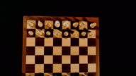 Footage of a chess board and its pieces lined up for a game start, the shot is from above the board and moves from the top to the bottom of the board video