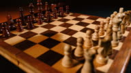 4K footage of a chess board and its pieces lined up for a new game start, a person makes the first move with a pawn video