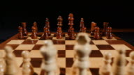 Footage of a chess board and its pieces lined up, the shot is taken behind white pieces looking into black ones video