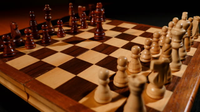 Footage of a chess board and its pieces lined up, two kings are being brought to the front video