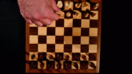 Footage of a chess board shot from above and it´s pieces lined up, a person is starting a new game video