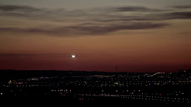 HD footage of a jet plane landing in silhouette against an orange sunset. video