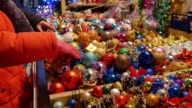 Footage of a table full of Christmas decorations and people looking to buy some Christmas tree balls video