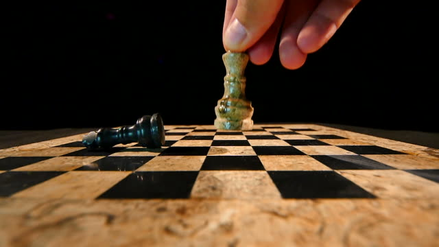 Footage of a white king chess piece hitting the black king who falls on the board and rolls away video