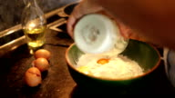 A footage of a woman preparing dough for making pancakes: a process of flour, eggs and milk being mixed together video