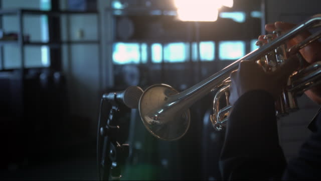 4K Footage of back side musician playing button and pushing on trumpet with microphone over the spot light in Music room background video