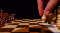 Footage of chess board with its pieces lined up, a person plays the first move with a pawn video