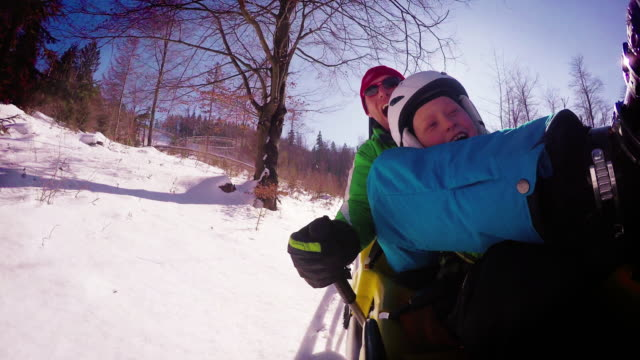 4K footage of father and son ehjoying winter bobsleigh attraction video