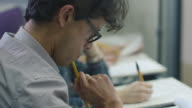 Footage of hispanic student writing with glasses in a collage classroom during lecture. video