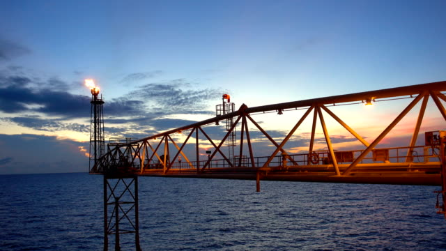 footage of oil and gas platform with flare burning bridge with sun rise and beautiful clouds in the morning for oil and gas industry concept. video