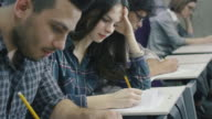 Footage of students writing with pens on paper in a collage classroom during lecture. video