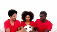 Football fans in red sitting on couch holding ball video