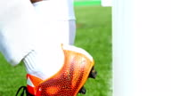 Football game. Soccer action. Goal keeper hits his orange shoes into the door and kicks the ball video